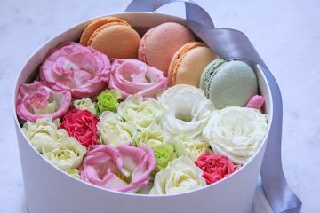round Box with flowers and almond cookies on marble background